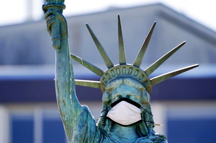 The face on a replica of the Statue of Liberty covers with a protective face mask against the coronavirus. The 1/18th scale replica on Seattle's Alki Beach was erected in 1952 and recast in 2006.