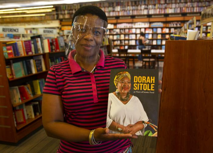"""Book store worker, Dikeledi Nhlapo, holds a copy of Dorah Sitole's """"40 Years of Iconic Food"""" cook book in Exclusive Books in Hyde Park Corner, Johannesburg."""