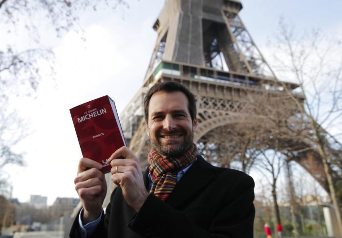 Gwendal Poullennec, head of Le Guide Michelin, poses outside the Eiffel Tower with the 2021 edition.