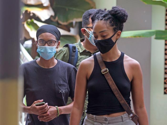 American graphic designer Kristen Antoinette Gray, left, walks with her partner Saundra Michelle Alexander, right, to be tested for the coronavirus at a hospital in Denpasar, Bali, Indonesia on Wednesday, Jan. 20, 2021