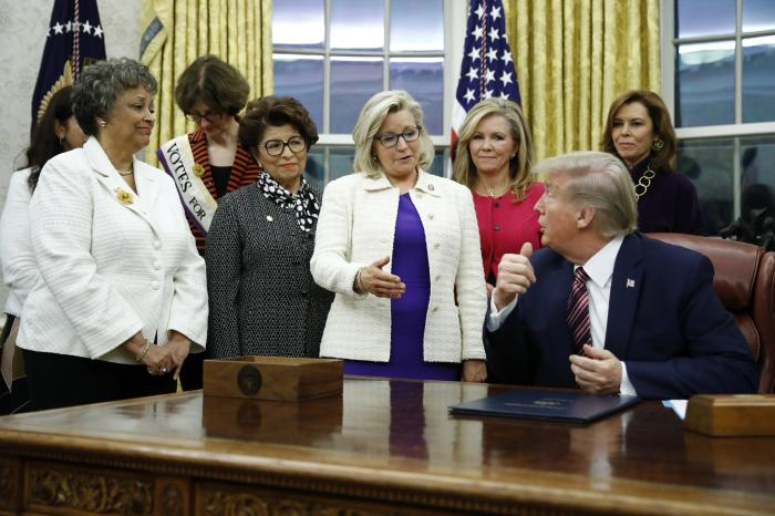 Rep. Liz Cheney, R-Wyo., center, speaks with President Donald Trump during a bill signing ceremony for the Women's Suffrage Centennial Commemorative Coin Act in the Oval Office of the White House in Washington.