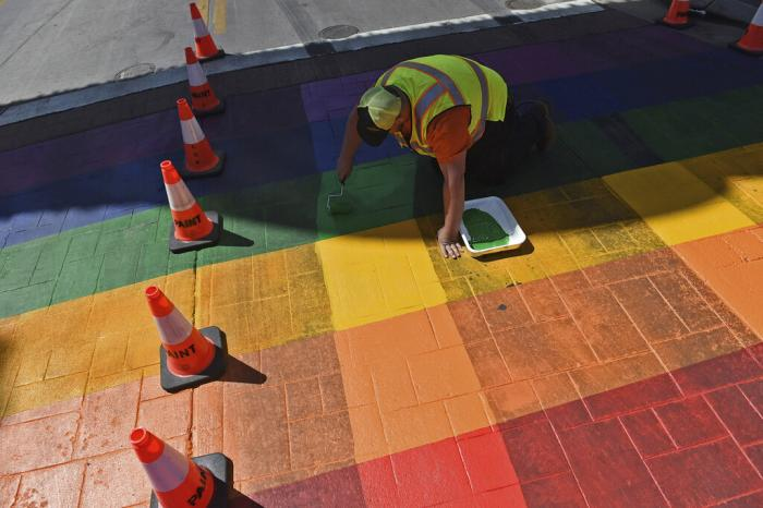 A city worker repaints the Pride crosswalk beneath the Reno Arch on Wednesday, June 9, 2021.