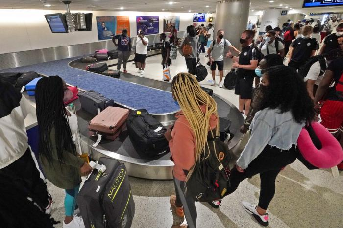 Travelers wait for their luggage at a baggage carousel at Miami International Airport in Miami.