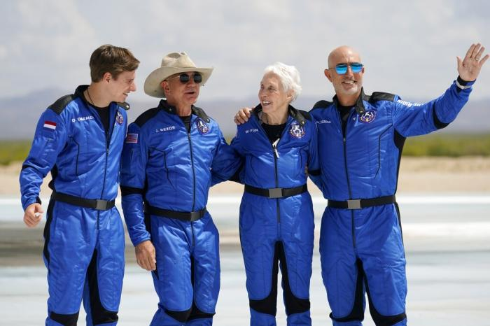 From left: Oliver Daemen; Jeff Bezos, founder of Amazon and space tourism company Blue Origin; Wally Funk; and Bezos' brother, Mark, pose for photos in front of the Blue Origin New Shepard rocket.