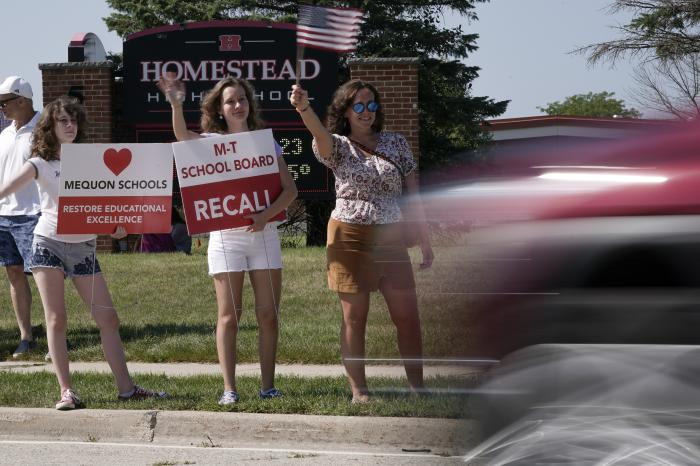 Supporters to recall the entire Mequon-Thiensville School District board wave at cars outside Homestead High School.