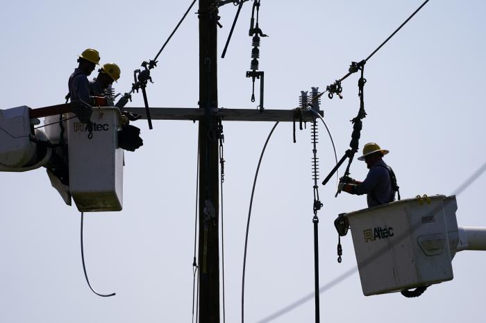 Crews work on power lines that were damaged in the aftermath of Hurricane Ida, Friday, Sept. 3, 2021, in LaPlace, La. (AP Photo/Matt Slocum)