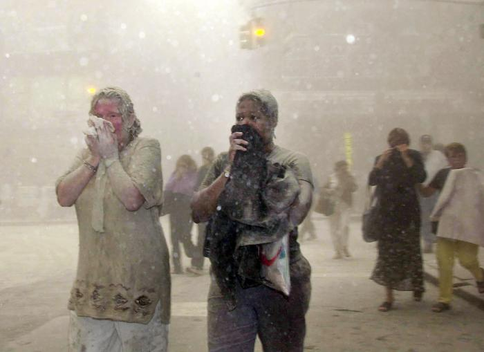 In this Sept. 11, 2001 file photo, people covered in dust from the collapsed World Trade Center buildings, walk through the area, in New York.