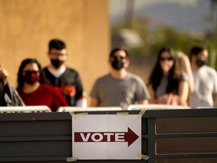 In this Tuesday, Nov. 3, 2020 file photo, Voters stand in line outside a polling station, on Election Day in Mesa, Ariz.